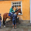 Mary King's daughter Emily makes tack adjustments with  Imperial Cavalier