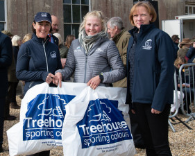 The groom of Tom Crisp picking up the Treehouse-sponsored award for best groomed horse