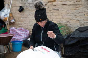 Tina Cook's groom, Rachel Tolley stitching a number onto the saddle pad of Star Witness