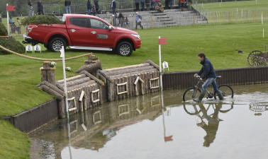 Chris Burton wheels his bike through the Lake whilst walking the course