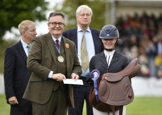 Alicia Hawker is presented with a saddle by Mr James Welch of the Worshipful Company of Saddlers with  The Duke of Beaufort and Mr Rob Lindley Managing Director of the Mitsubishi Motors  Badminton Horse Trials