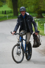 Mark Todd multi-tasking, as he juggles the handle bars and the boots